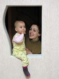 Mother with baby in window. Mother with baby in figure window royalty free stock photo