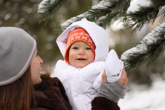 Mother with baby in Winter. Smiling baby in snow suit with mother in Wintry park royalty free stock images