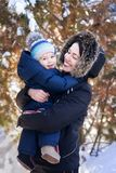 Mother and baby on winter walk. Happy mother and baby boy hugging on winter walk outdoor royalty free stock images