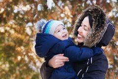 Mother and baby on winter walk. Happy mother and baby boy hugging on winter walk outdoor royalty free stock image