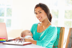 Mother With Baby Working In Office At Home Royalty Free Stock Images
