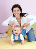 Mother  with babygirl. Mother plays with babygirl on bed Royalty Free Stock Photo