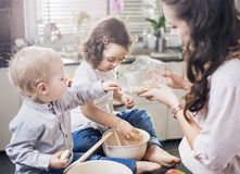 Mother baking a cake with her children. Mother baking a sweet cake with her children stock photos