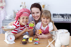 Mother baking with children in the kitchen. Happy mother baking with children in the kitchen stock images