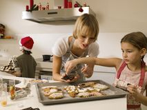 Mother baking cookies with her children. Stock Images