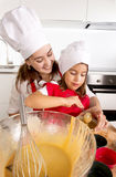 Mother baking with little daughter in apron and cook hat filling mold muffins with chocolate dough Stock Photo