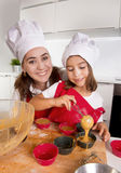 Mother baking with little daughter in apron and cook hat filling mold muffins with chocolate dough Stock Photography