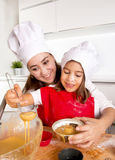 Mother baking with little daughter in apron and cook hat filling mold muffins with chocolate dough Stock Image