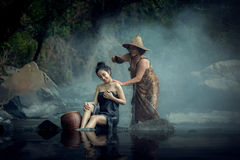 Mother bathes a beautiful Asian daughter in a brook with running Stock Image