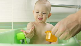 Mother bathing attractive baby. The boy is smiling and playing with colorful toys and water. Kid for about a year.  stock video