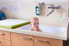 Mother bathing baby in hospital room Stock Images