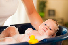 Mother is bathing her baby Stock Image