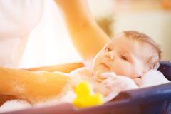 Mother is bathing her baby in bathtub Royalty Free Stock Images