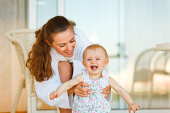 Mother in bathrobe playing with baby on terrace Royalty Free Stock Photos