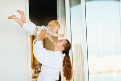 Mother in bathrobe playing with baby on terrace Stock Images