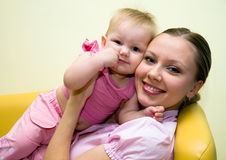 Mother with beautiful baby. Portrait of happy mother with beautiful baby on the yellow sofa Stock Photos
