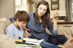 Mother Becoming Frustrated With Son Whilst Doing Homework Sitting On Sofa At Home Stock Image
