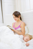 Mother in bedroom reading book while baby sleeping Royalty Free Stock Photography