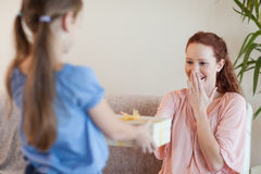 Mother being surprised by daughter with present Stock Photography