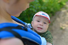 Mother and beutiful baby walking outdoors, happy boy smiling  looking to the camera Stock Images