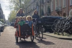 Mother and kids riding bicycle in Amsterdam. A mother with a bike and carrier with four kids bicycling down the street in Amsterdam royalty free stock photos