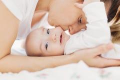 Mother biting her baby's cheek Stock Photo