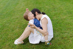 Mother Biting Laughing Daughter. Mother biting her laughing daughter on grass stock photography