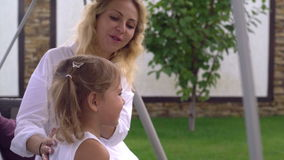 Mother with blond hair take care about little daughter. stock video