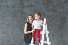 Mother and blond son on a step-ladder Stock Images