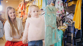 Mother with blonde daughter buying sweatshirt - kids clothes in store Stock Photography