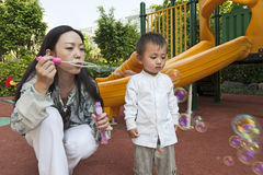 Mother blowing bubbles for son Royalty Free Stock Image