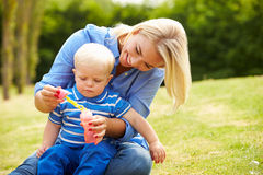 Mother Blowing Bubbles For Young Boy In Garden Stock Photo