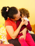 Mother blowing her child's nose. Mother blowing her daughter's nose Royalty Free Stock Images