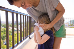Mother blowing nose to little child in terrace Stock Photos