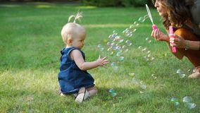 Mother Blowing Soap Bubbles to her Baby stock footage