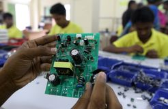 Mother board of a solar optimizer. Dhaka 27 August 2014. An employee works on a mother board of a solar optimizer, a key component of solar home systems in Royalty Free Stock Photo
