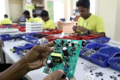 Mother board of a solar optimizer. Dhaka 27 August 2014. An employee works on a mother board of a solar optimizer, a key component of solar home systems in Stock Photography