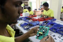 Mother board of a solar optimizer. Dhaka 27 August 2014. An employee works on a mother board of a solar optimizer, a key component of solar home systems in Stock Image
