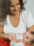 Mother bottle feeding baby. Contented baby being bottle fed by Mother Royalty Free Stock Photography