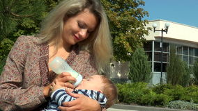Mother bottle feeding baby stock video footage