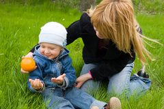 Mother and boy. Mom and the son play with an orange on a grass. Spring Stock Photo