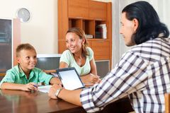 Mother and boy answer questions. Mother and teenage boy answer questions of outreach worker in home royalty free stock image