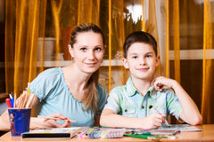Mother and boy doing homework together stock images