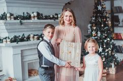 Mother, boy and girl dressed elegantly standing in a bright room by the fireplace. Family keep a wooden clock stock image