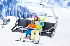 Mother with boy lifting on ski lift Royalty Free Stock Image