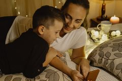 Mother and boy looking into the phone in bed before going to sle Royalty Free Stock Photography