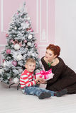 Mother with boy near fir tree with gift Stock Images