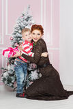 Mother with boy near fir tree with gift Stock Image