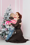 Mother with boy near fir tree with gift Royalty Free Stock Photos