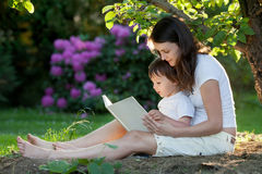 Mother and boy, reading a book, summertime in a garden, nice sun. Mother and boy, reading a book, summertime in a garden, beautiful sunset light Royalty Free Stock Images